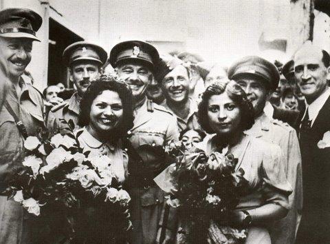 Jeunes femmes juives de Libye lors d'une réception avec des couronnes de fleurs pour l'armée et les soldats britanniques