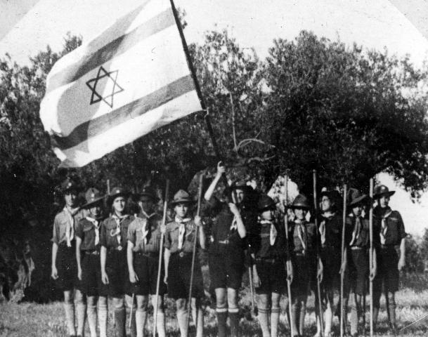 """חברות תנועת הנוער בית""""ר במדי התנועה אוחזות דגל."""