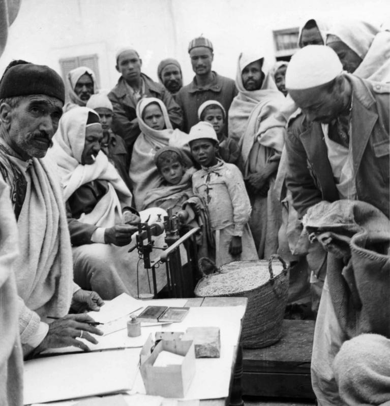 Jewish saleswoman weighing wheat on the Gharian market and Arab spectators. Jewish community of mountain dwellers (Troglodyte Jews) in Gharian, Libya, 1947.