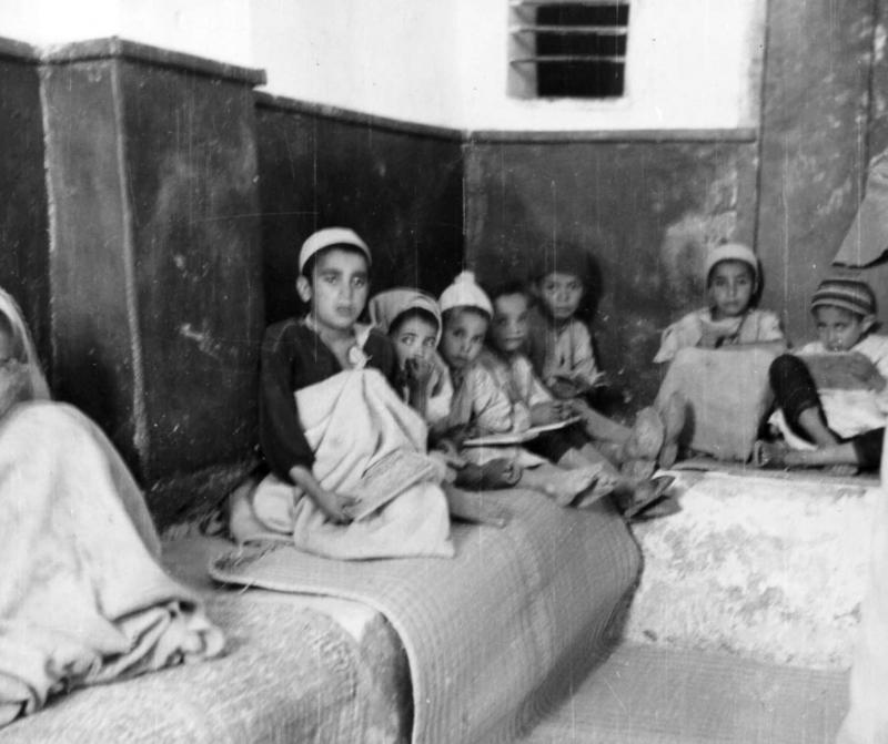A teacher and his pupils in Talmud Torah class in the new synagogue of the troglodyte Jewish community in Gharian, Libya, 1947.