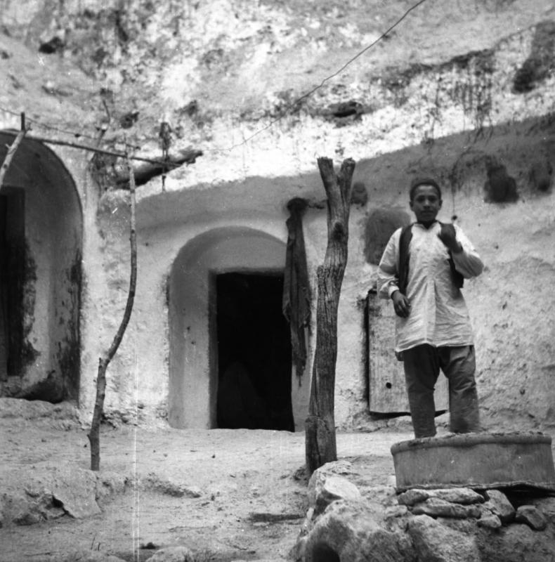 Un garçon dans la cour d'habitations excavées dans la roche (cavernes) de la communauté juive de Gharian, Libye, 1947