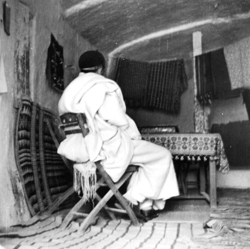 Man sitting on a chair in a house excavated in rock-excavated dwellings (underground caverns). Photo of the community of Mountain Jews (Troglodyte Jews) in Gharian, Libya, 1947.