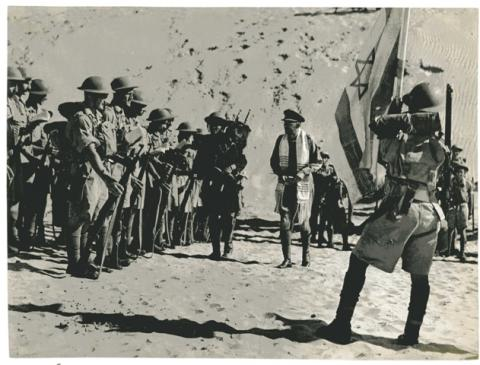 "<a href=""/en/node/2799"">חייל מפלוגת מכבי נושא ספר תורה, עובר בין חיילי הפלוגה לפני צאתם לקרב מול האויב הנאצי</a>"