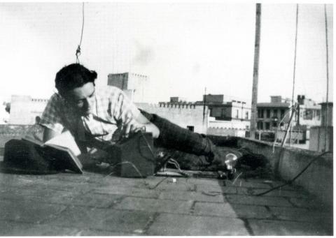 "<a href=""/he/2891"">דן אפרת רוכן על מכשיר רדיו שהרכיב ומאזין לשידורי BBC בניגוד לחוקי הכיבוש הגרמני. תוניס, 1942</a>"