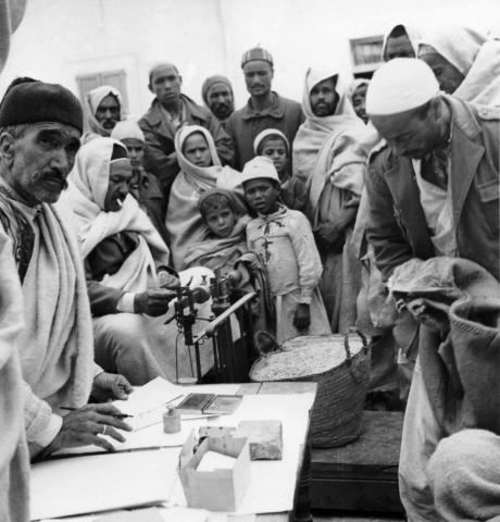 "<a href=""/en/2907"">Jewish saleswoman weighing wheat on the Gharian market and Arab spectators. Jewish community of mountain dwellers (Troglodyte Jews) in Gharian, Libya, 1947.</a>"
