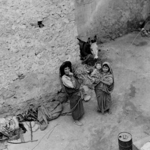 """<a href=""""/en/2903"""">Girls in the yard doing housework (piling up twigs for burning and looking after a baby), Gharian, Libya 1947</a>"""